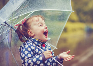 A little girl enjoys the rainfall.