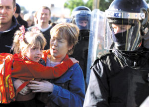 A Catholic school student and her mother make their way to Holy Cross Roman Catholic school under a heavy police and British Army presence in the Ardoyne area of north Belfast, Northern Ireland, Tuesday, Sept. 4, 2001. Protestants in the bitterly divided north Belfast neighborhood of Ardoyne hurled rocks, bricks, bottles and even flower pots at the heavily girded officers protecting the girls as they arrived for school. (AP Photo/Peter Morrison)
