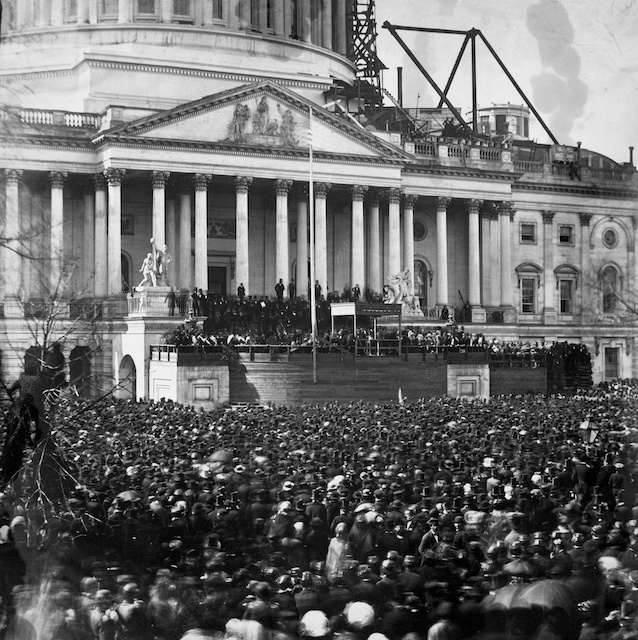 participants and crowd at the first inauguration of President Abraham Lincoln, at the U.S. Capitol, Washington, D.C. Lincoln is standing under the wood canopy, at the front, midway between the left and center posts. His face is in shadow but the white shirt front is visible.  (Wikipedia/Library of Congress).